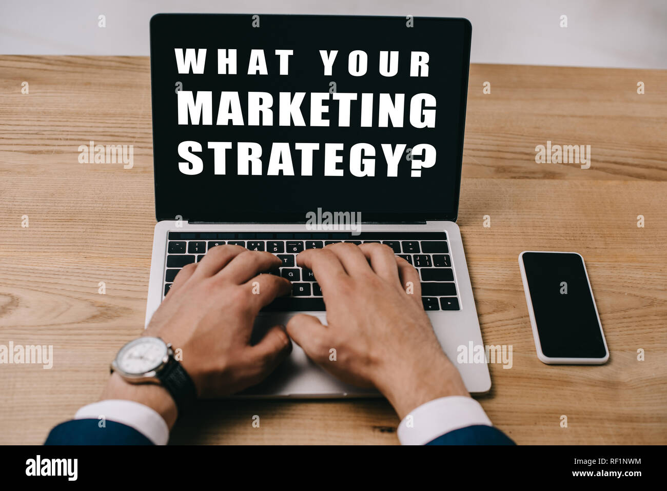 cropped view of businessman typing on laptop with what your marketing strategy? - Stock Image