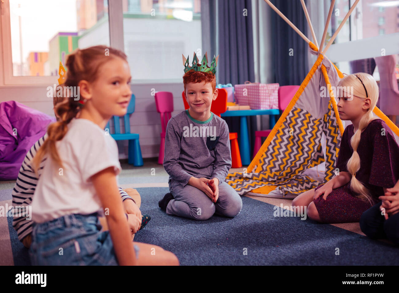 Pleased boy wearing paper crown during playing - Stock Image