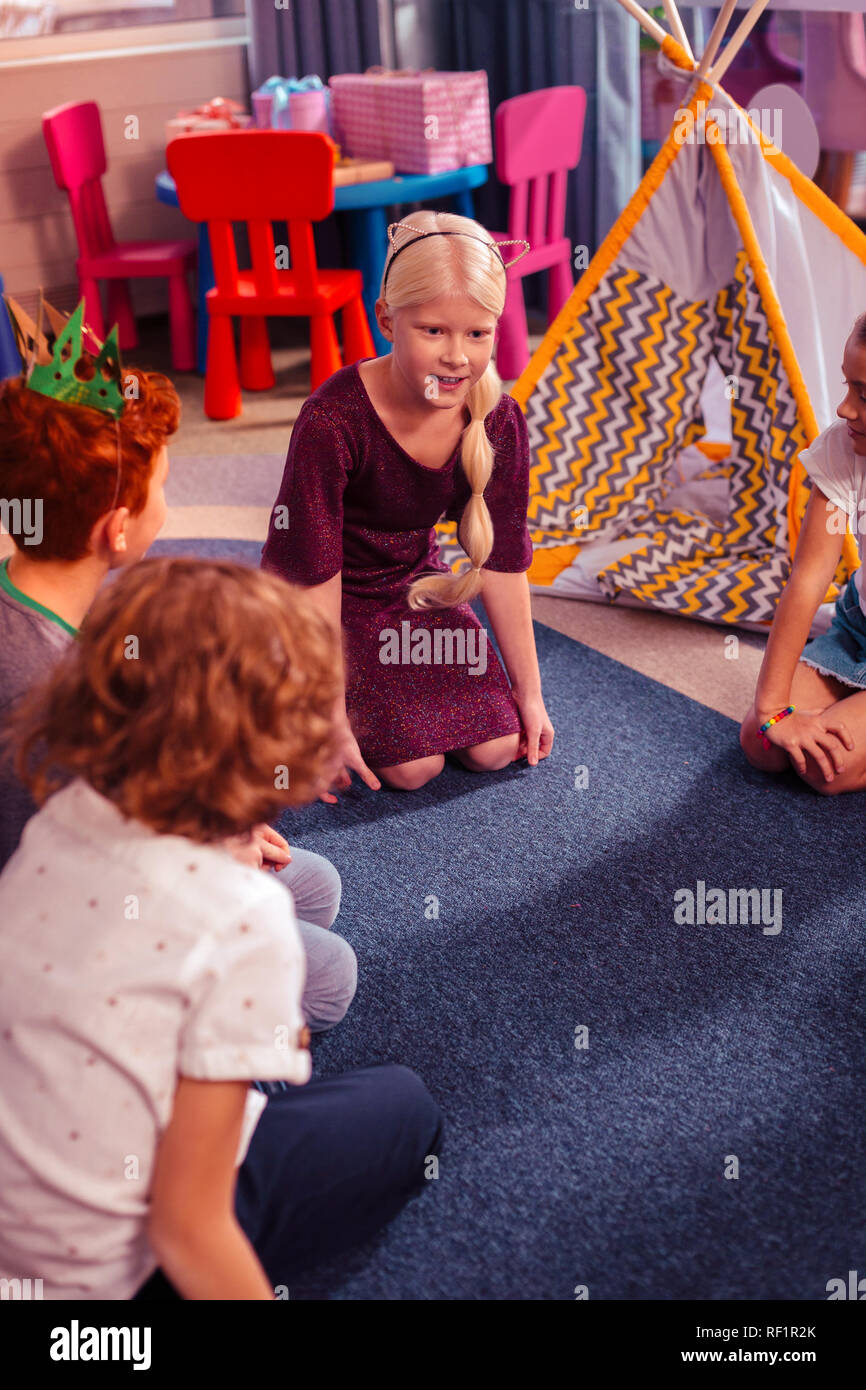 Cheerful blonde little female talking to her classmates - Stock Image