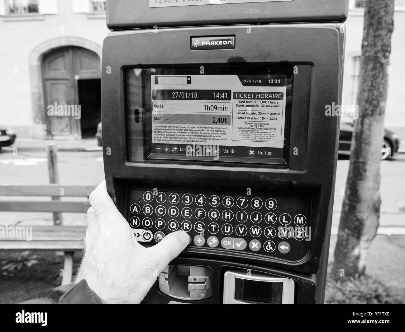 STRASBOURG, FRANCE - JAN 27, 2018: Man hand operating digital electronic park metere in French city of Strasbourg, setting time on the digital touchscreen - Stock Image