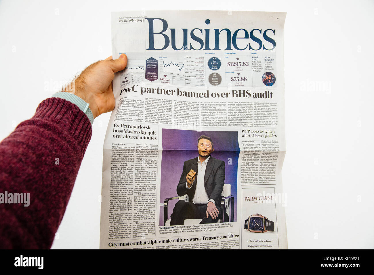 PARIS, FRANCE - JUN 13, 2018: Man holding The Daily Telegraph with portrait of Elon Musk CEO of tesla saying he is cutting 9 percent of jobs - Stock Image