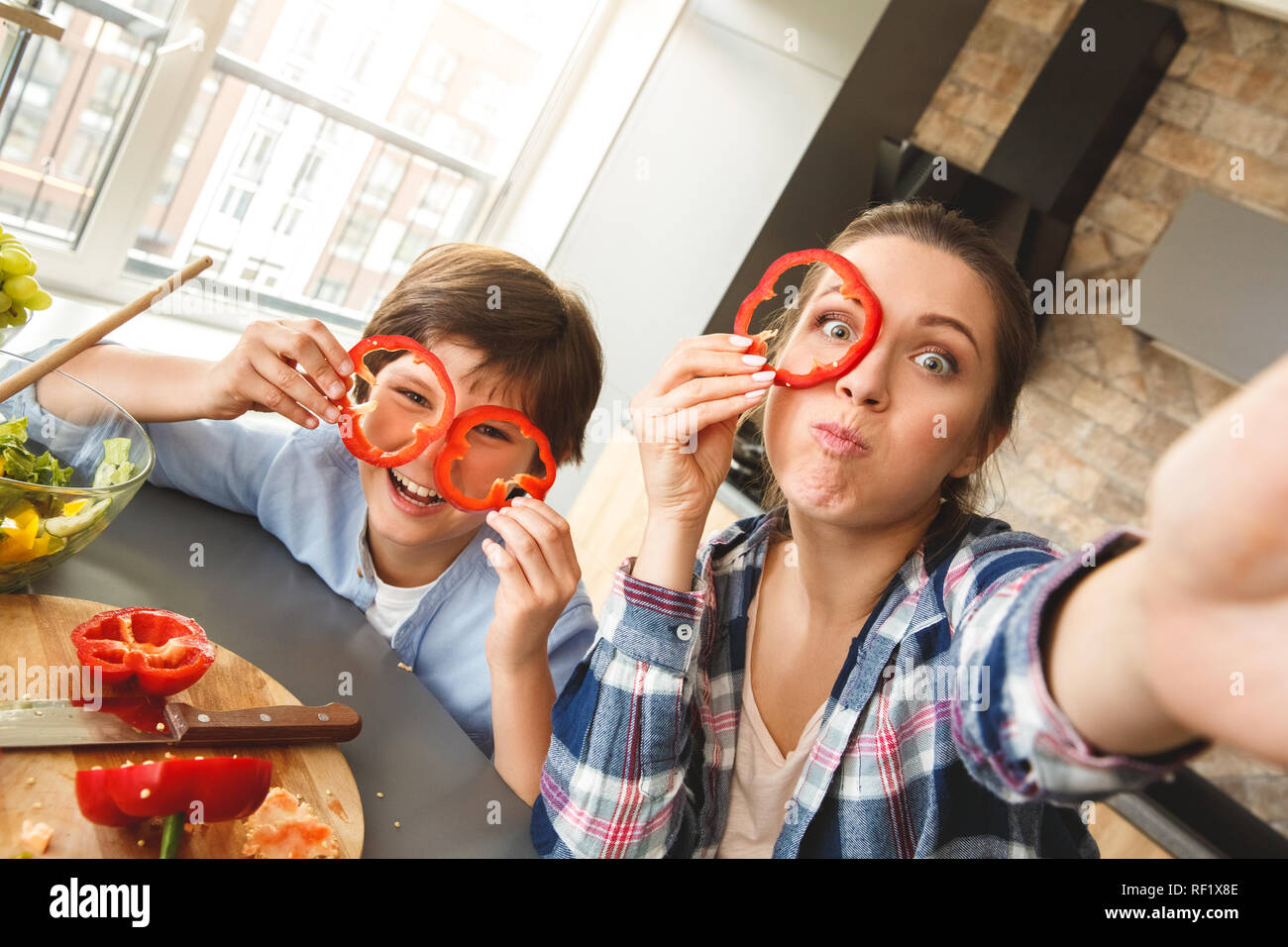 Family at home standing in kitchen together taking selfie photos looking camera grimacing covering face with bell pepper circles - Stock Image