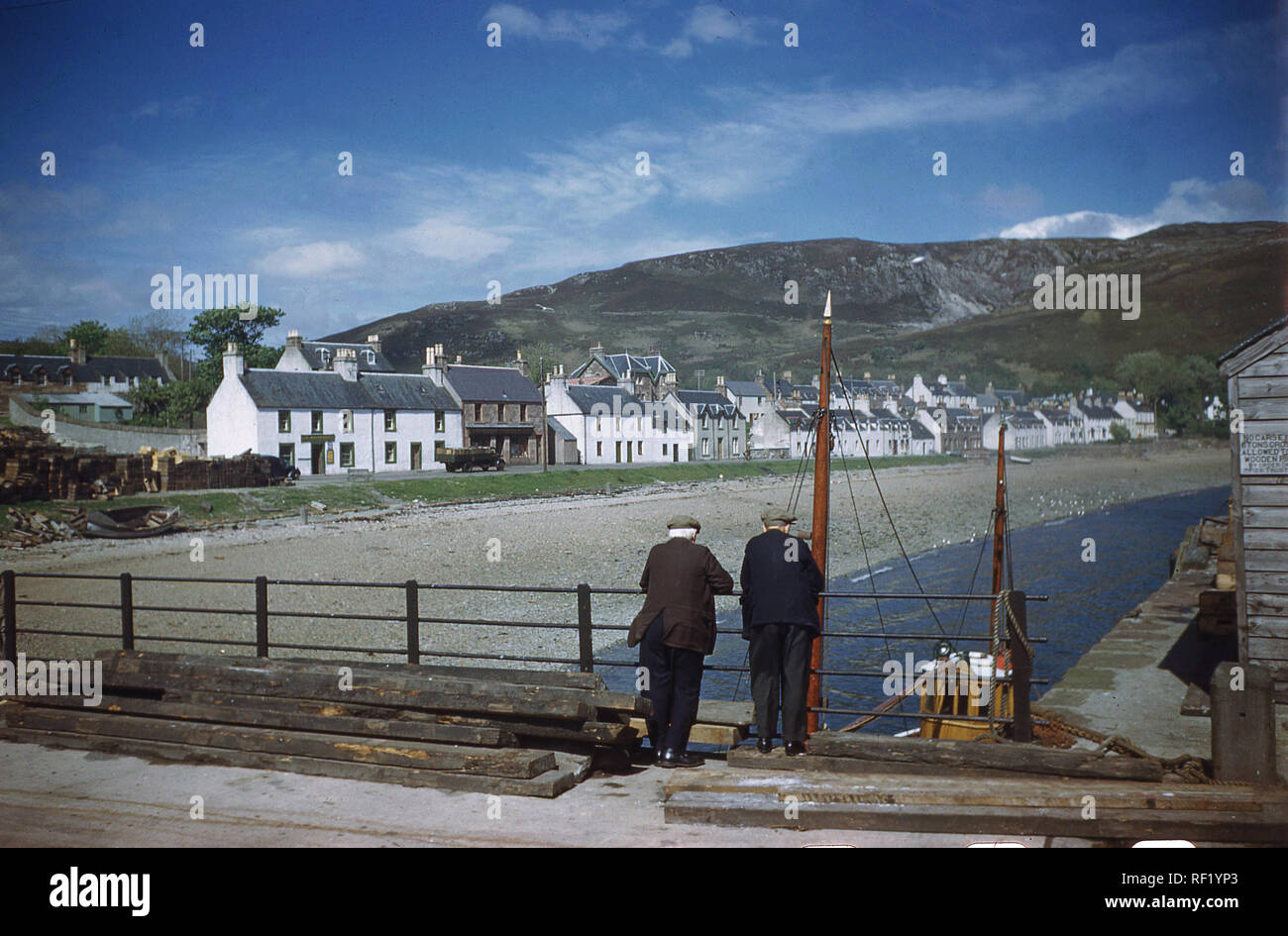 1960s, historical, two local men standing on a bridge at the harbour looking backwards to highland village of Ullapool, Highlands, Scotland, UK. Stock Photo