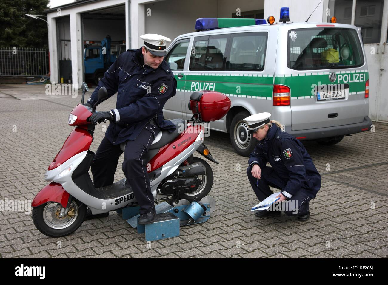 Police officers checking a small moped that has been manipulated and tuned, Mettmann, North Rhine-Westphalia - Stock Image