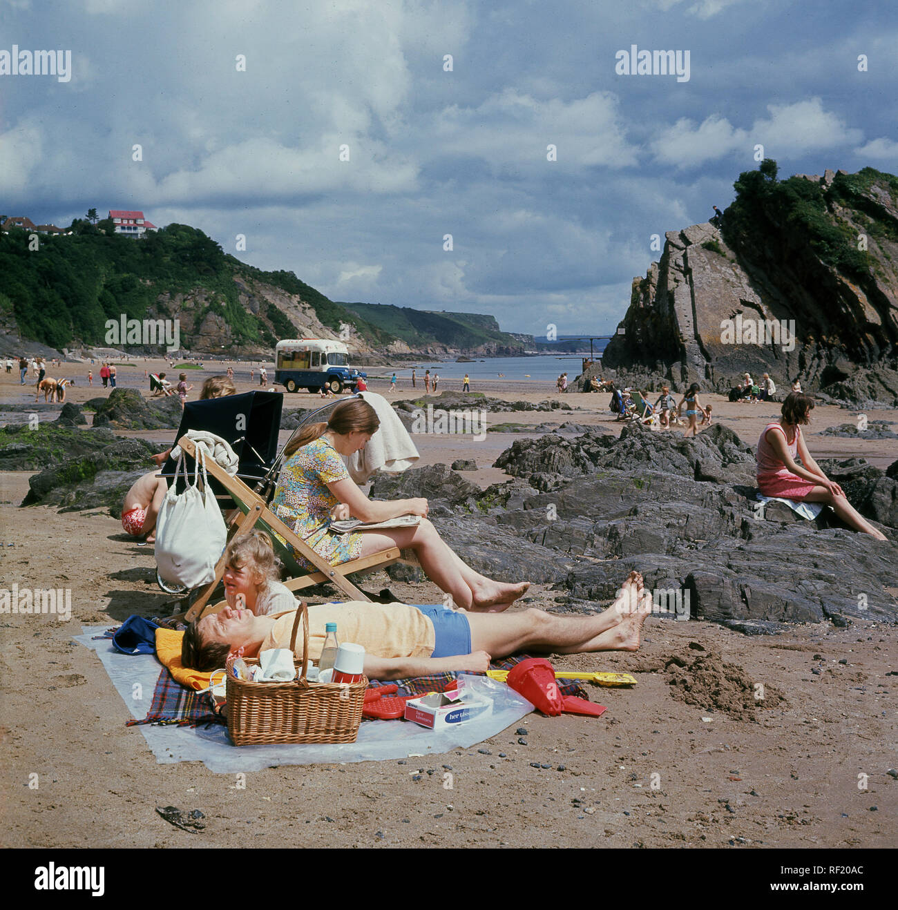 1960s, historical, traditional British family holiday...a day on the beach..a family relaxing on Tenby beach, Wales, UK. The man lies on a rug next to the lunch basket, while his wife sits in a deckchair reading. - Stock Image