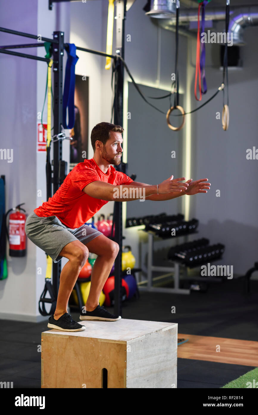 Man doing box jumps in a gym - Stock Image