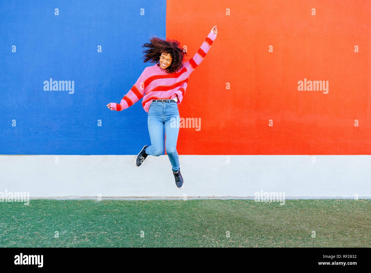 Happy young woman jumping in the air - Stock Image