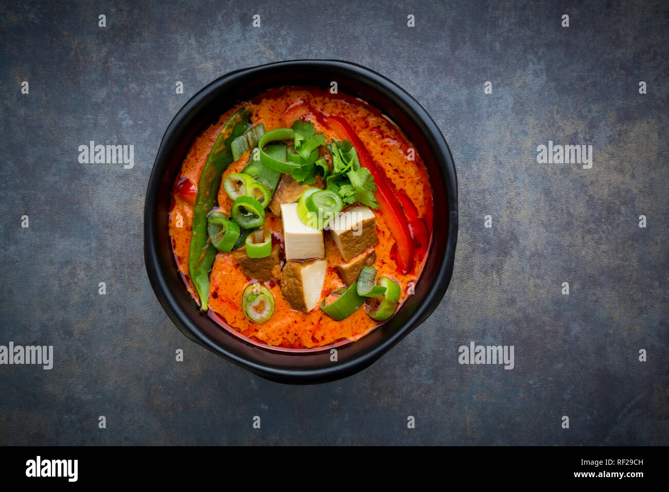 Bowl of red Thai Curry with snow peas, carrots, bell pepper, spring onions and smoked tofu - Stock Image