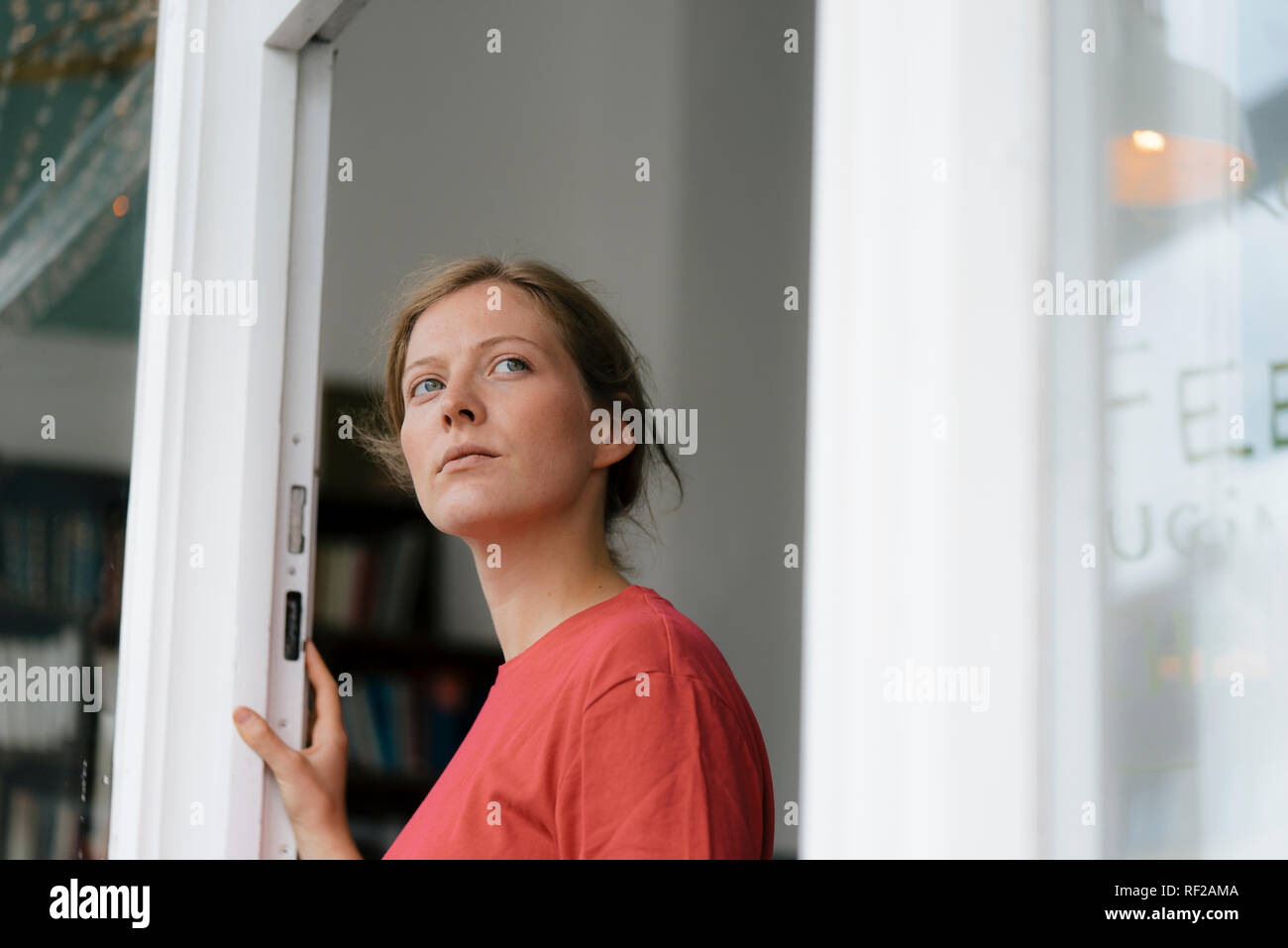 Young woman at French door in a cafe looking around - Stock Image