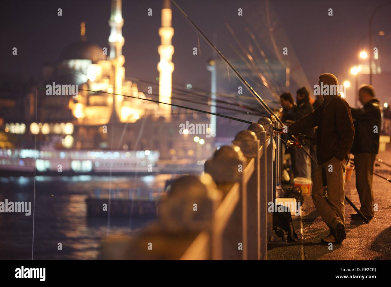 Fishermen at Galata Bridge over the Golden Horn, two-storied road bridge, traffic above, bars and restaurants below, Istanbul - Stock Image