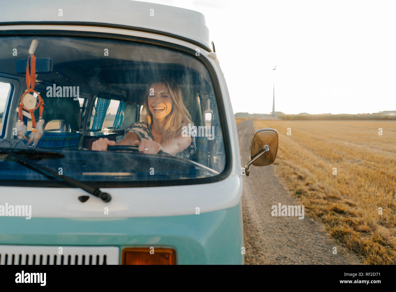 Happy young woman driving camper van in rural landscape Stock Photo