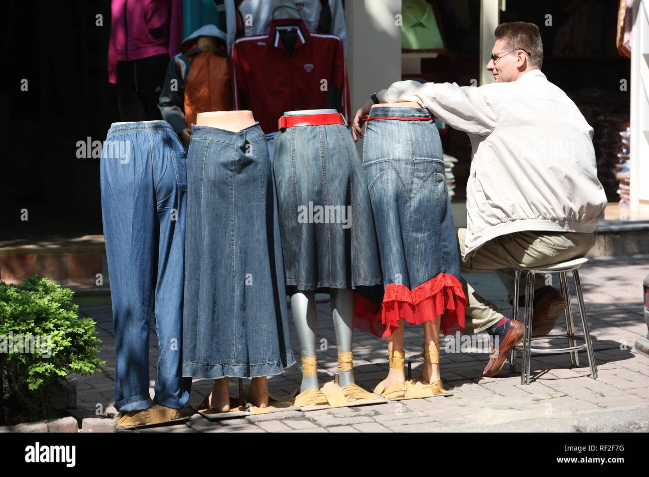 Street trader with jeans skirts on a bazar in Sultanahmet, Istanbul, Turkey - Stock Image