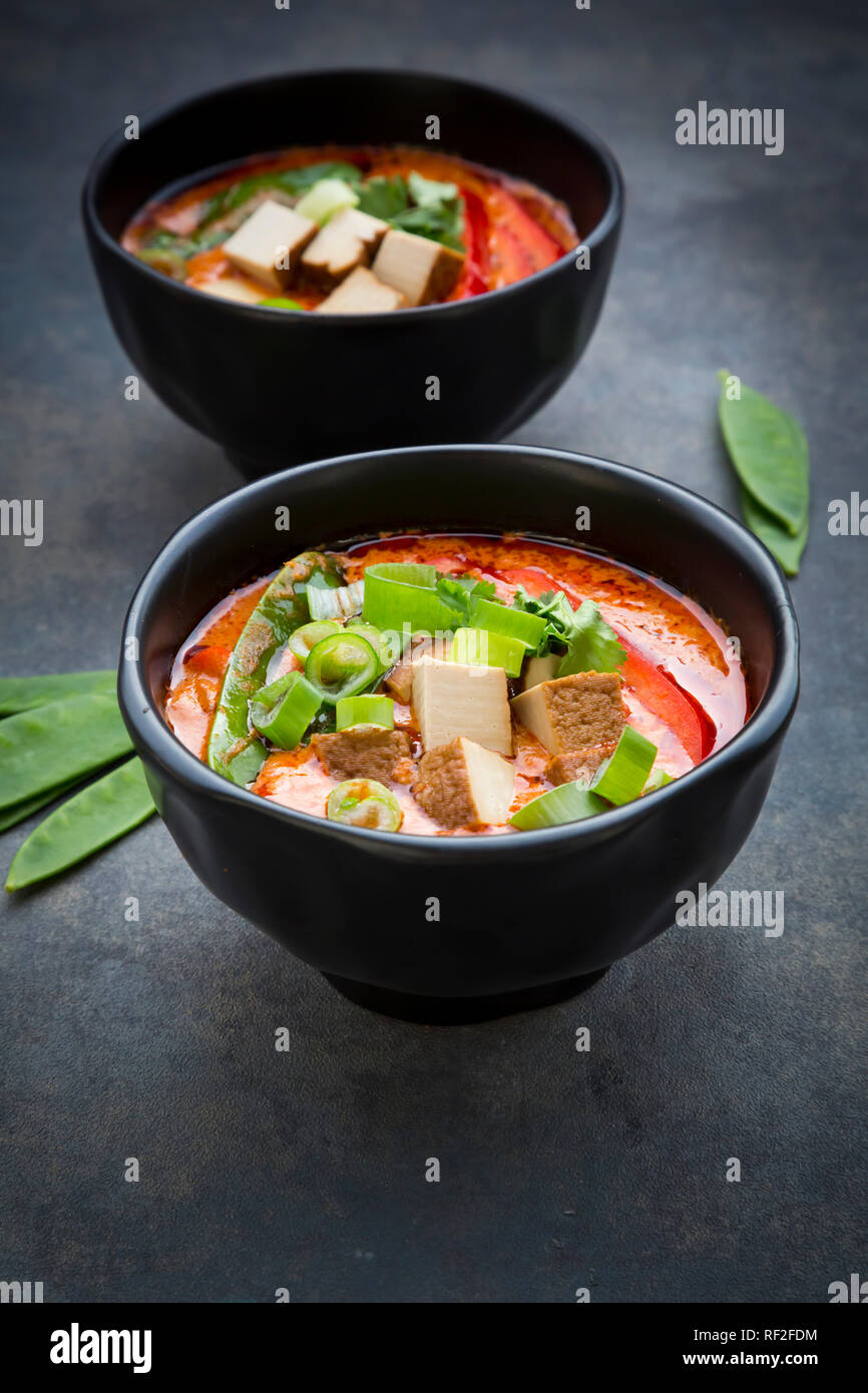 Bowls of red Thai Curry with snow peas, carrots, bell pepper, spring onions and smoked tofu - Stock Image