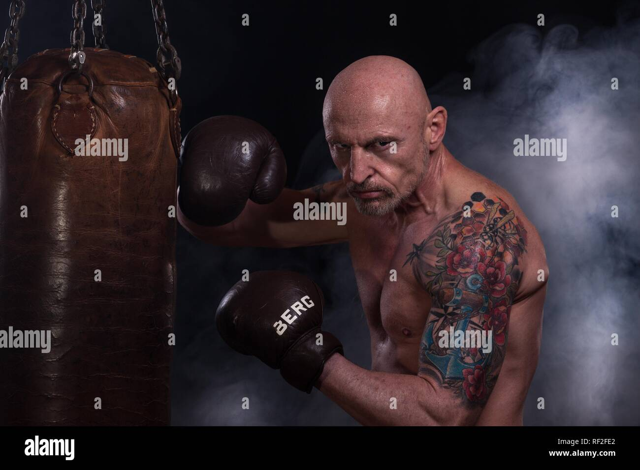 Man, bald and tattooed, with boxing gloves, trained on punching bag, Germany - Stock Image
