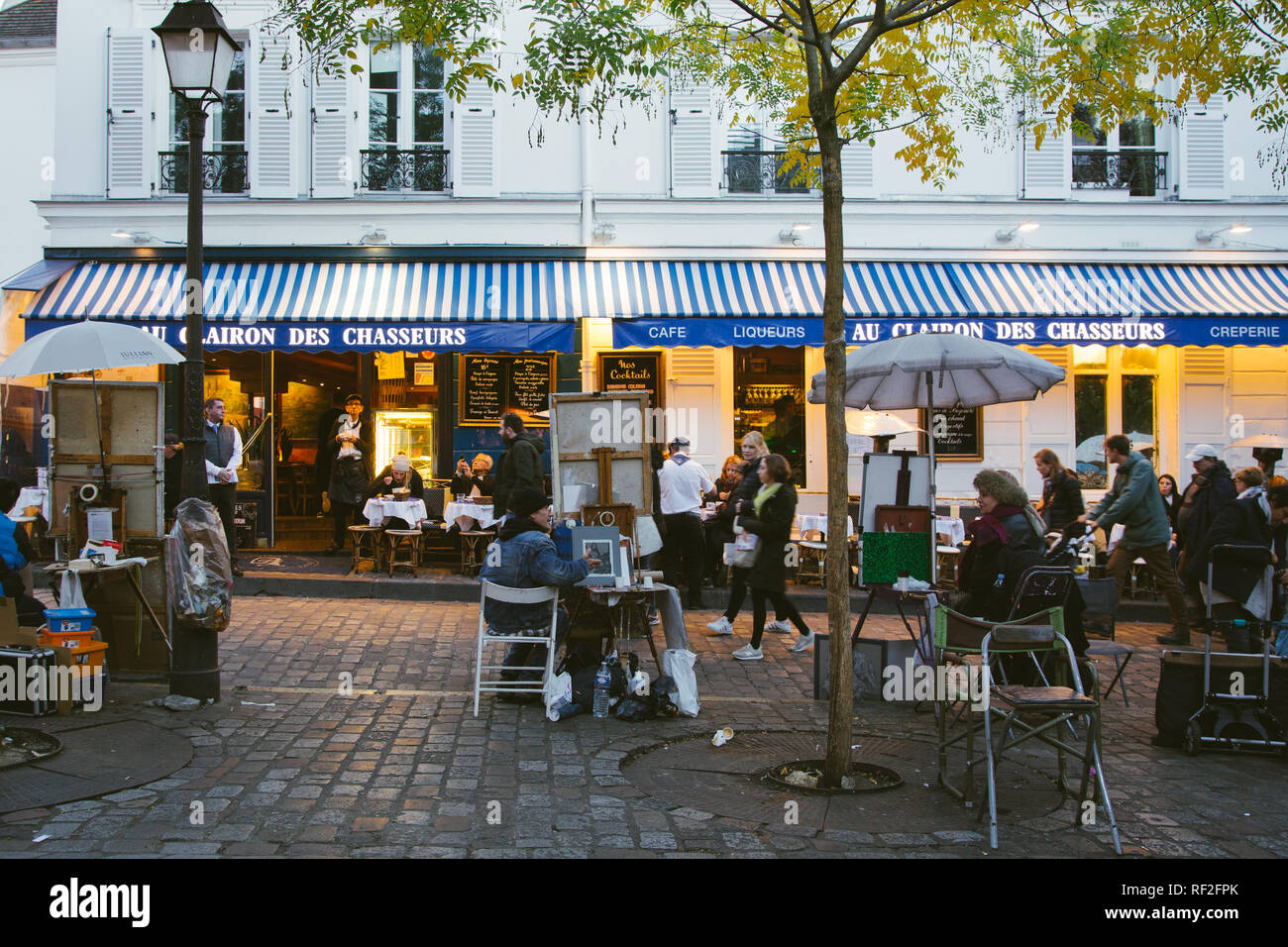 PARIS, FRANCE - NOVEMBER 9, 2018 - Cozy street with cafe and painters in Montmartre, Paris Stock Photo