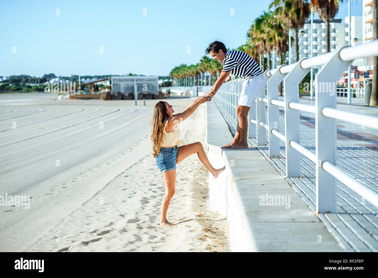 Man helping woman to climb up from the beach to the promenade - Stock Image