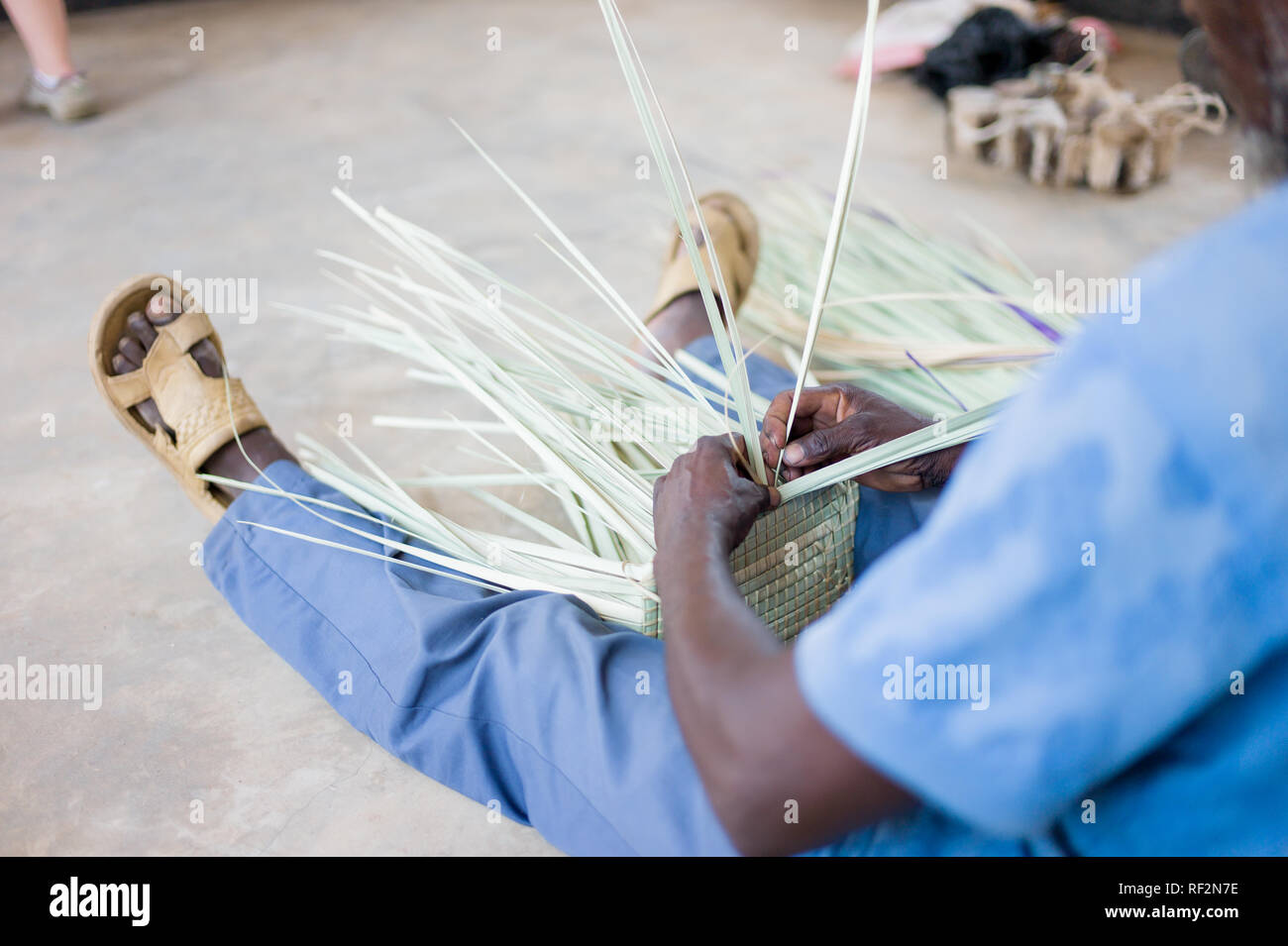 A Malawian man weaves baskets as part of a community outreach program of Majete Wildlife Reserve in Malawi; local communities craft souvenirs to sell - Stock Image