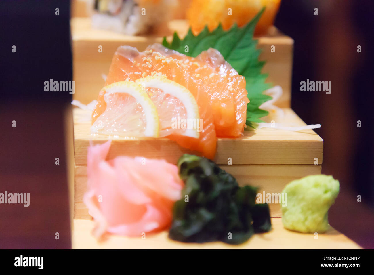 Japanese Fresh Fish Food Dish Menu,  Salmon Sashimi, seaweed, ginger and wasabi decorated on wooden step in traditional Japanese Restaurant. Healthy F Stock Photo