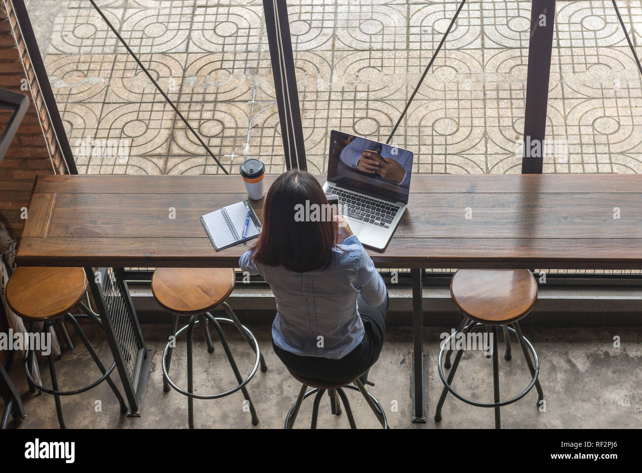 Rear view photo of Asian businesswoman checking email on phone Stock Photo