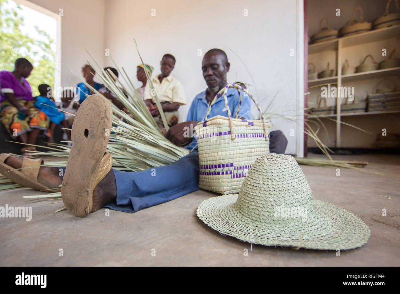 A Malawian man weaves baskets for a community outreach program of Majete Wildlife Reserve, Malawi; Cmmunity members craft souveniers to sell - Stock Image