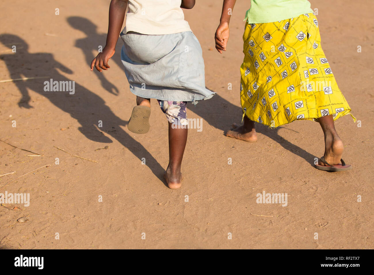 Malawian girls play in their village near Chikwawa; they are sharing a pair of flip flop sandals. Stock Photo