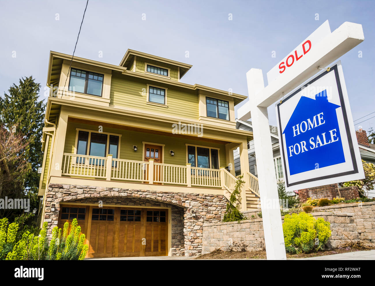 Home with a 'for Sale' sign in front of it. - Stock Image