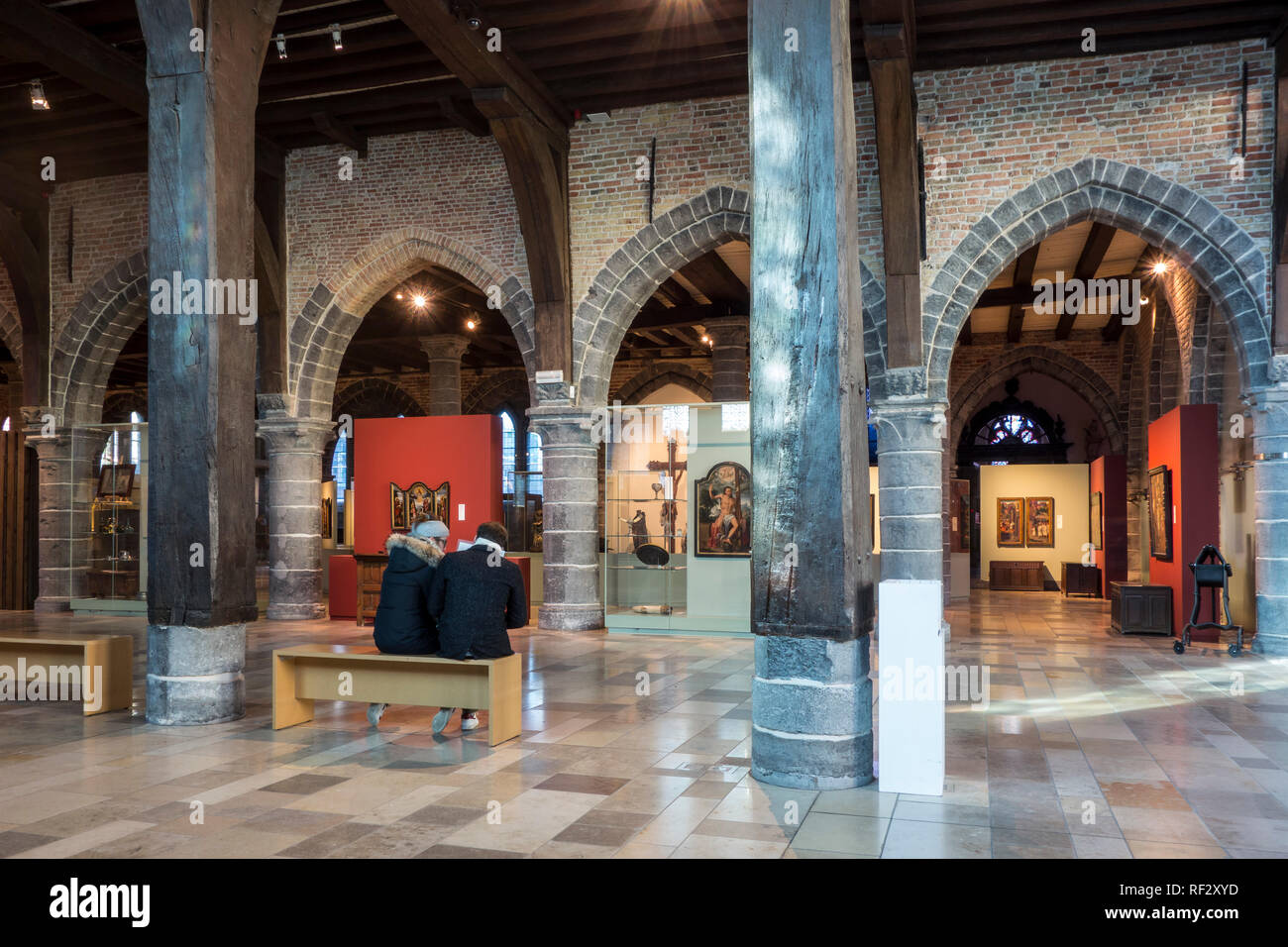 Tourists visiting museum in the old sick-bay at the medieval Sint-Janshospitaal / St John's Hospital in the city Bruges, West Flanders, Belgium - Stock Image