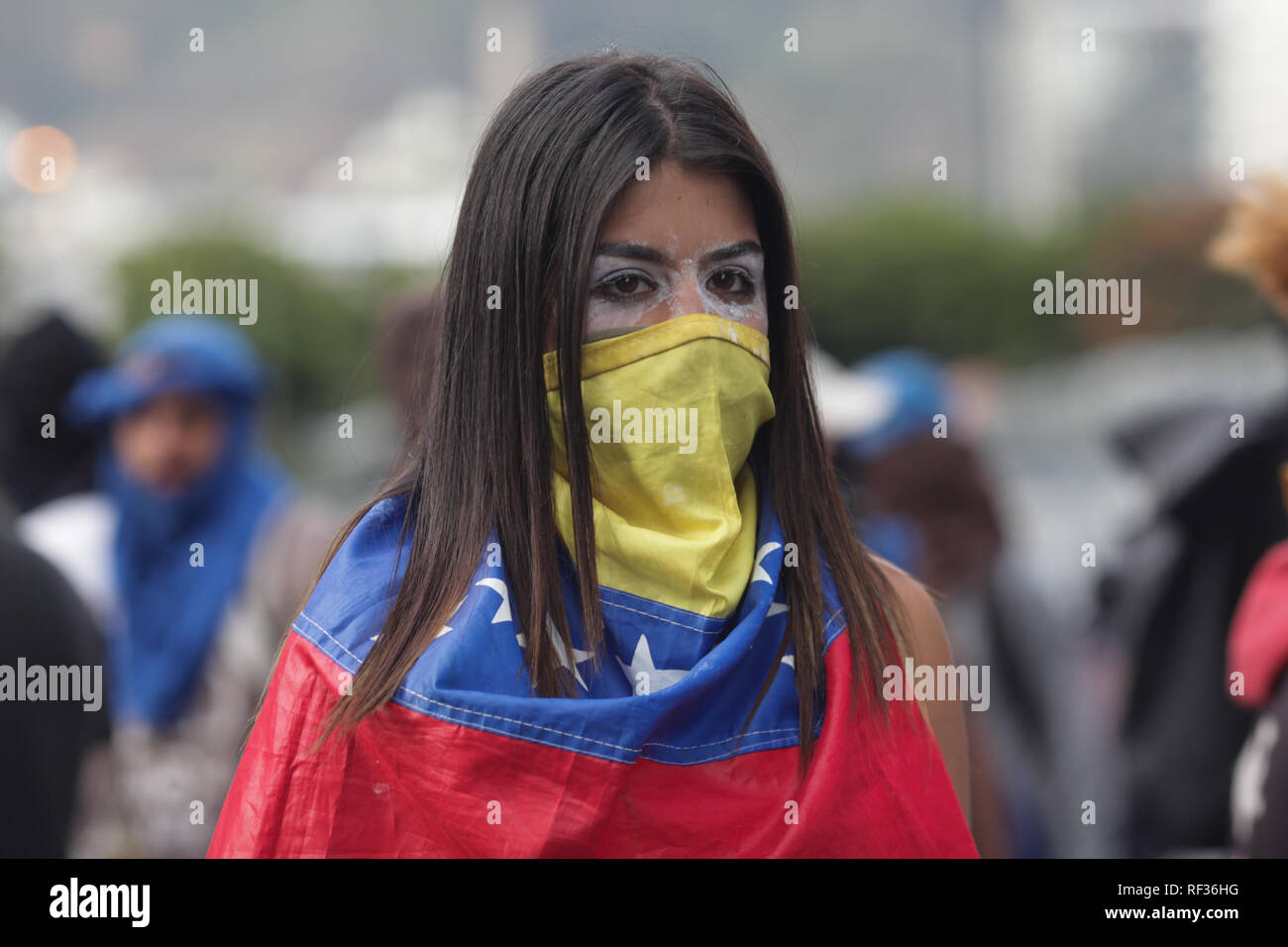 Caracas, Venezuela. 23rd Jan, 2019. A woman has masked herself with a Venezuelan flag and is protesting against the Venezuelan President Maduro. Venezuelan parliamentary president Guaidó has declared the socialist government of Maduro to be deprived of power and has proclaimed himself head of state in transition. Minutes later, US President Donald Trump recognized the opposition leader as the legitimate interim president of the corruption- and poverty-stricken country. dpa/Alamy Live News - Stock Image
