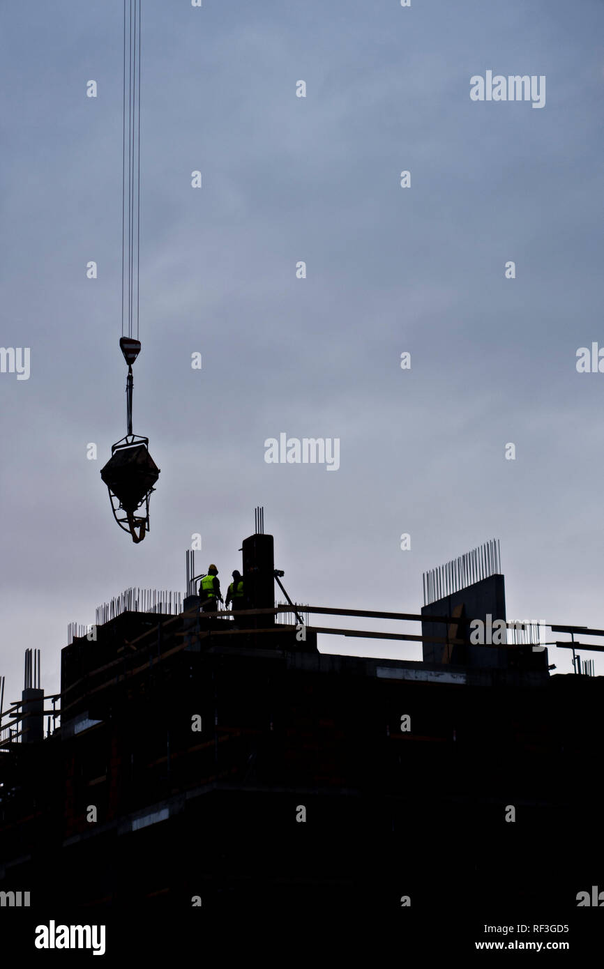 silhouette of workers during the construction of a residential multi story building - Stock Image