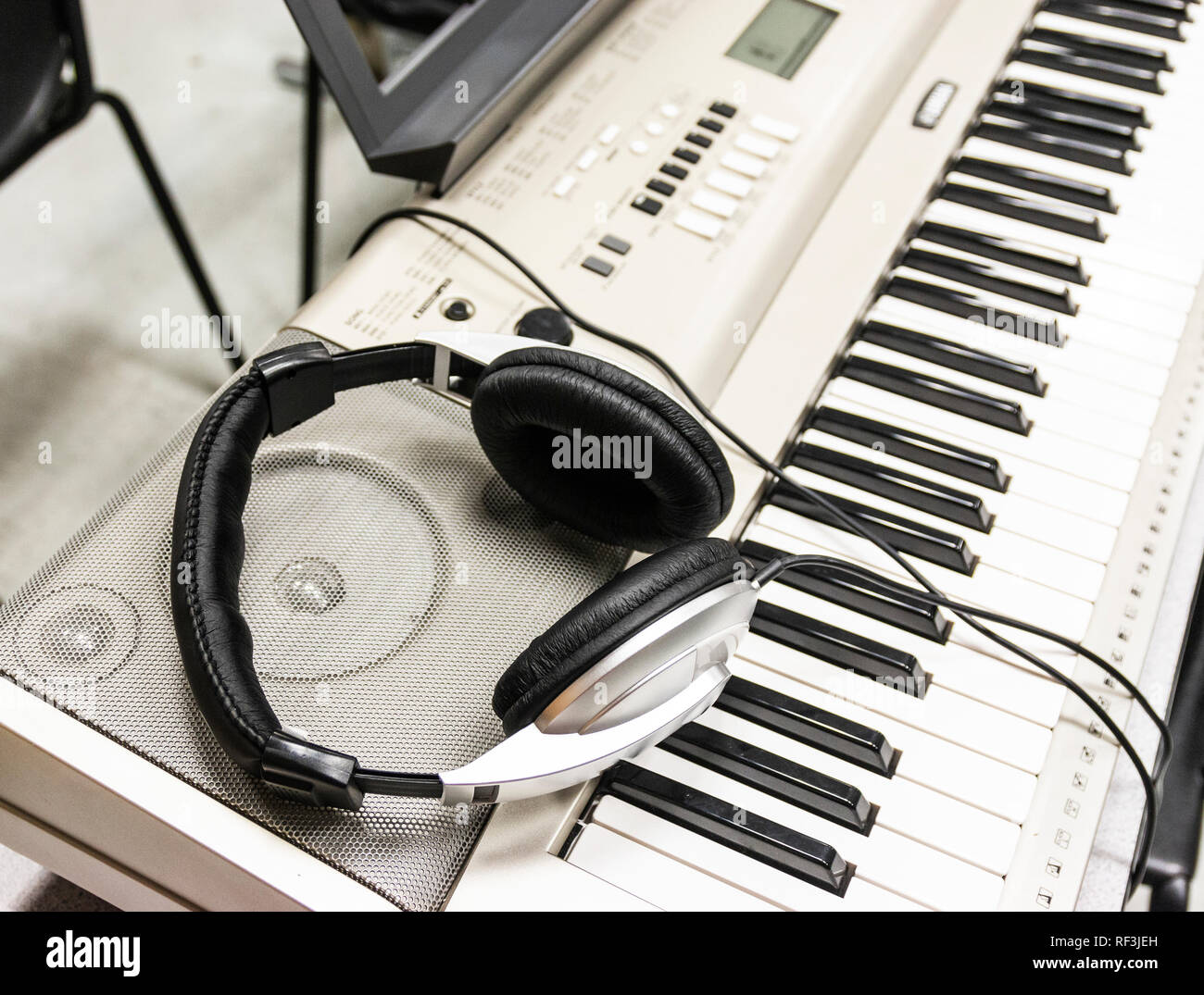 Headphones are resting on the speakers of an electric piano. - Stock Image