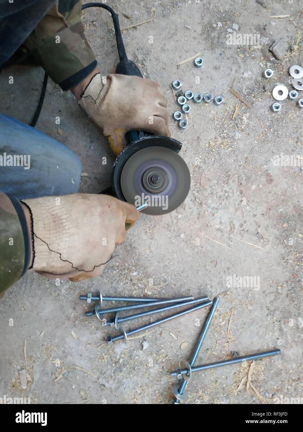 the worker uses an angle grinder to sharpen the bolts, a close-up plan 2019 - Stock Image