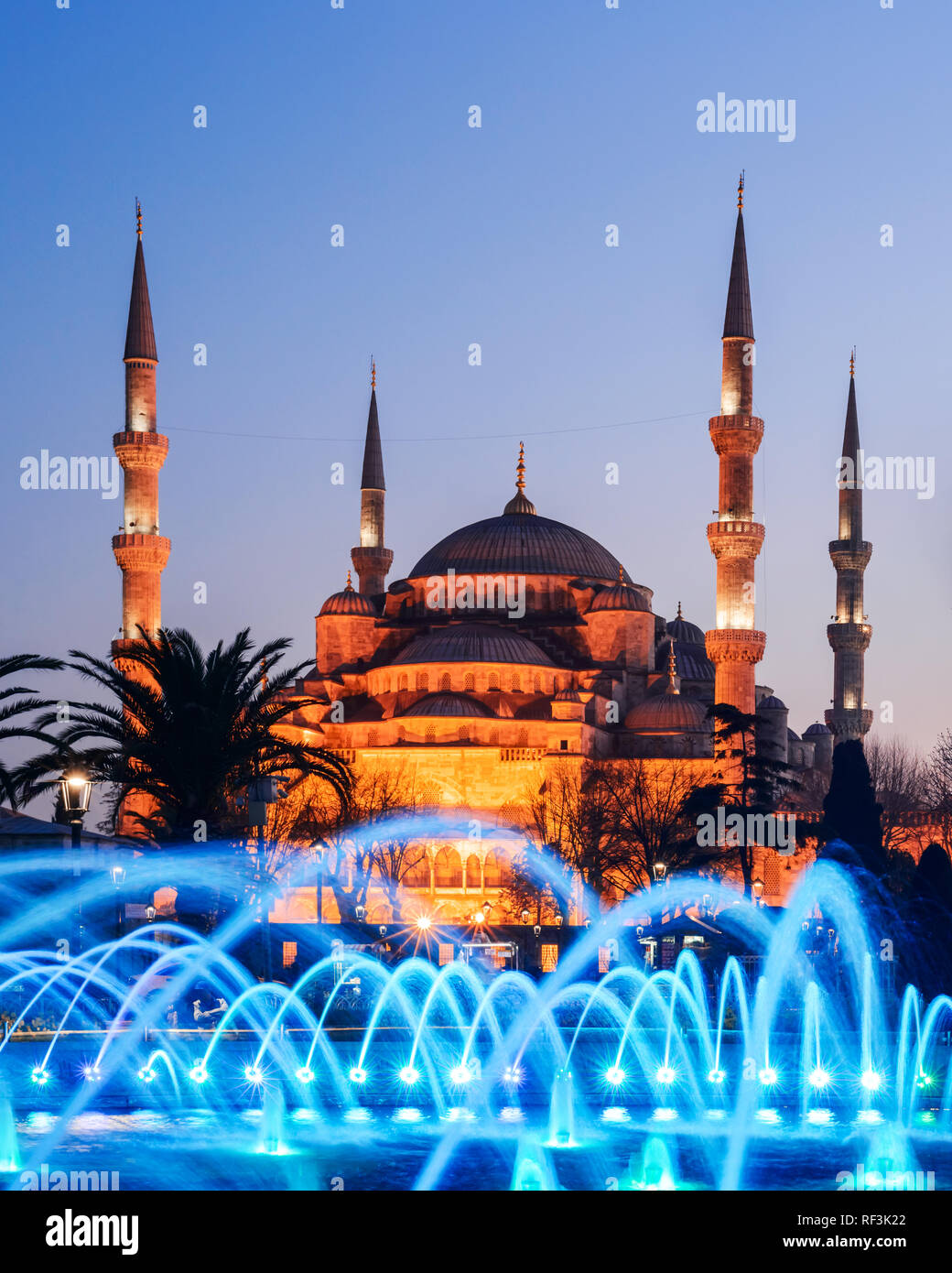 Fountain on Sultanahmet area in evening time. Multicolored streams against the background of the Blue mosque. Located place: Istambul, Turkey - Stock Image