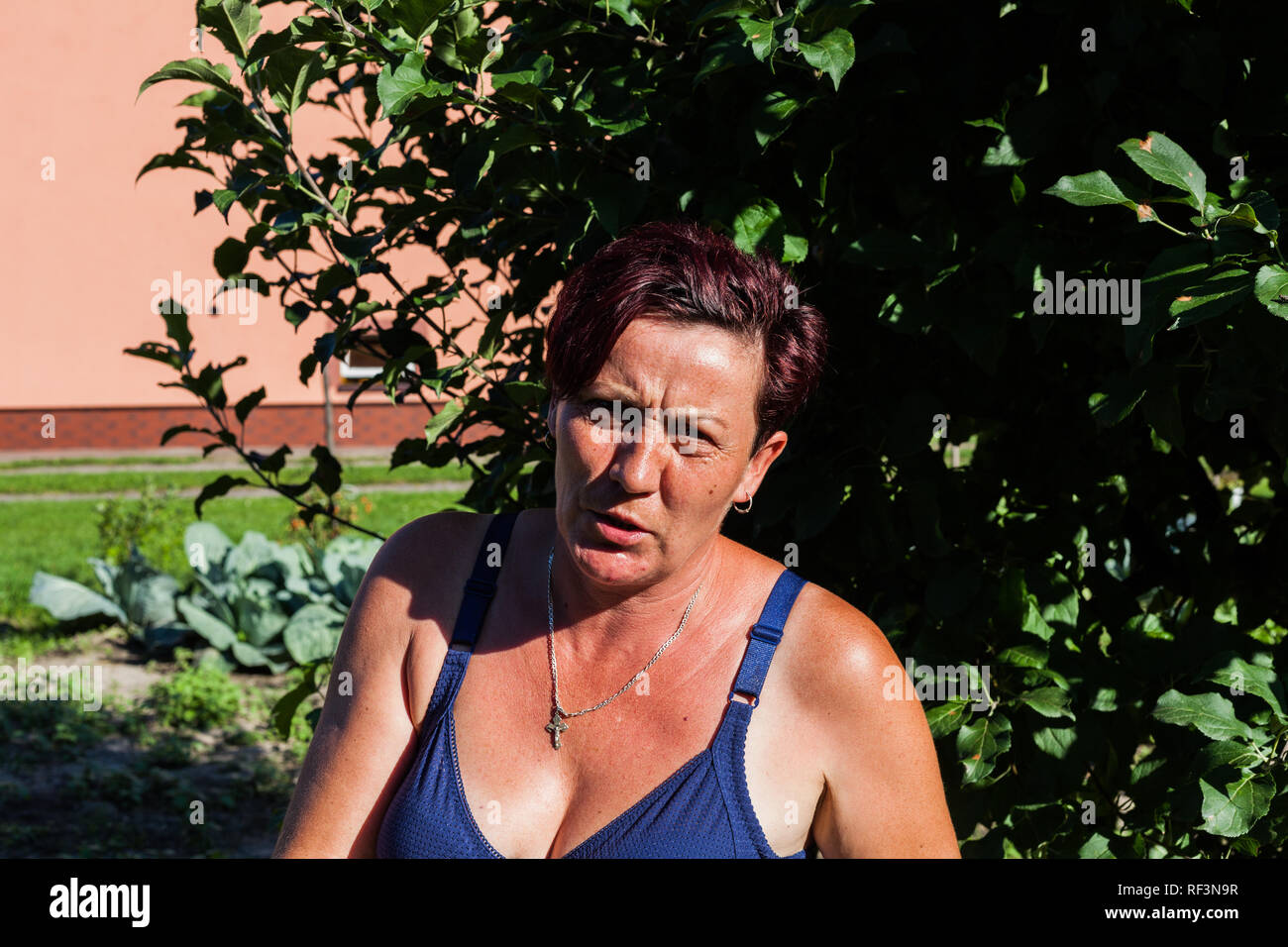 Focused view of a woman looking fiercely in one sunny day. The brunet housewife wearing brassiere behind the tree. Summer fashion style. Typical hot d - Stock Image