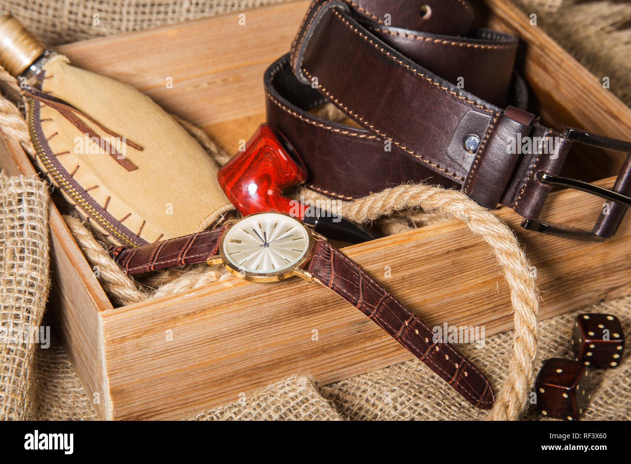 Men's accessories with brown leather belt, sunglasses, watch, smoking pipe and bottle with perfume on rustic background. Stock Photo