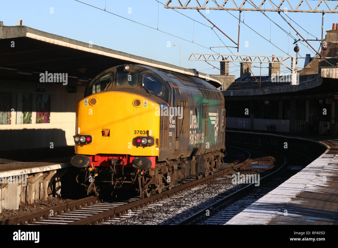 Class 37 diesel-electric loco in Direct Rail Services livery on light engine working passing through Carnforth station platform 2 on 23 January 2019. - Stock Image