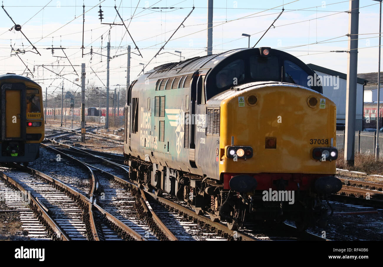Class 158 dmu in Northern livery joining West Coast Main Line and passing class 37 diesel-electric locomotive arriving at Carnforth from the WCML. - Stock Image