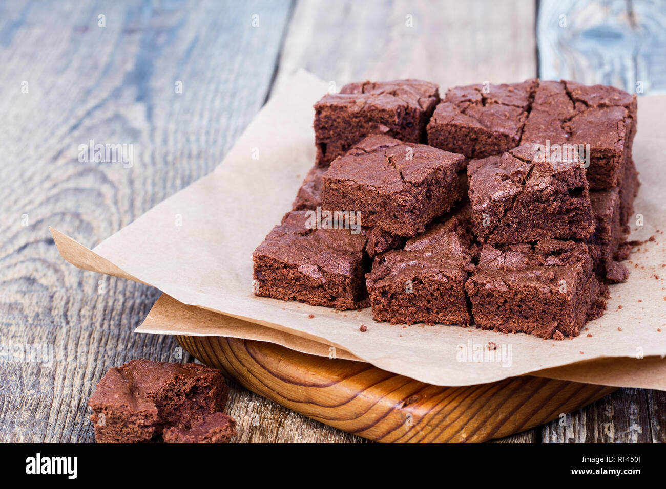Pieces of freshly baked chocolate brownie on rustic wooden board, close-up, selective focus - Stock Image