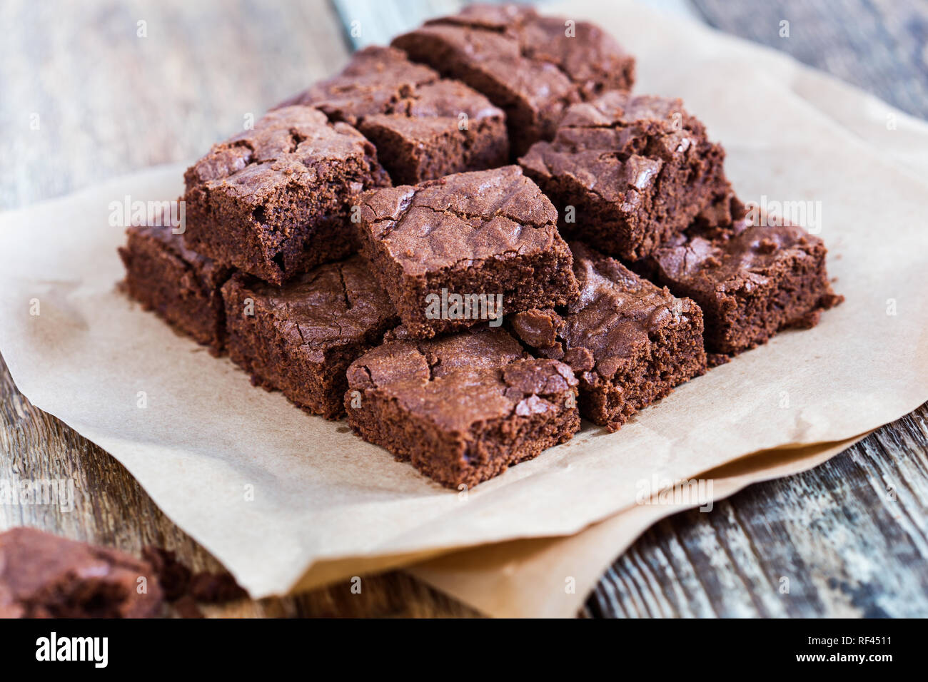 Pieces of freshly baked chocolate brownie on rustic wooden board, close-up, selective focus Stock Photo