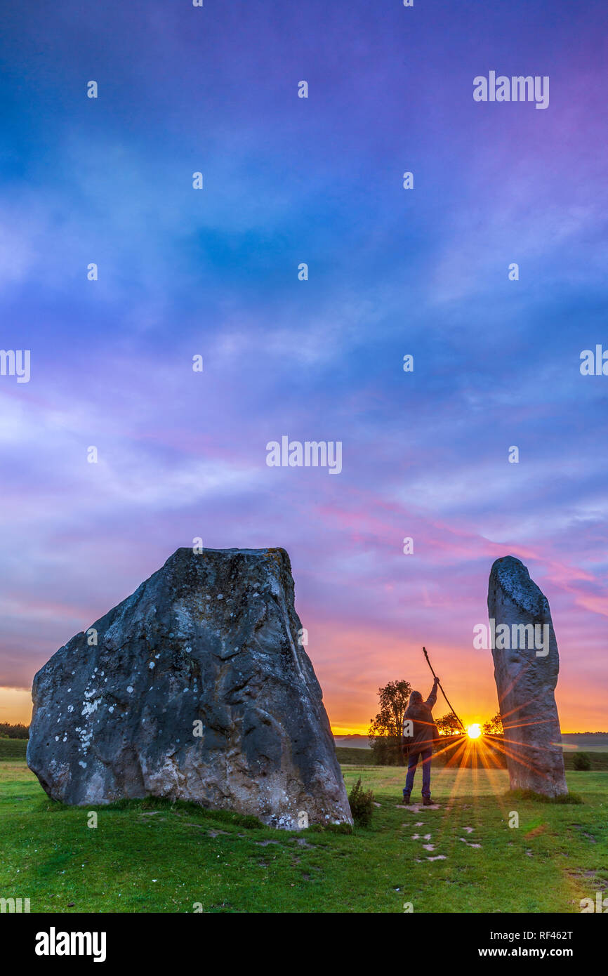 An image of a Druid greeting the sun, between the giant Sarsen stones of Avebury in Wiltshire, the day before the Solstice.  Image captured using a Ni Stock Photo