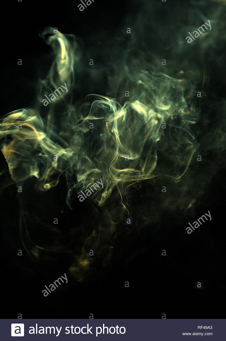 Green morning sunlight passing through rising smoke from a dying campfire creating an ethereal abstract mood. - Stock Image