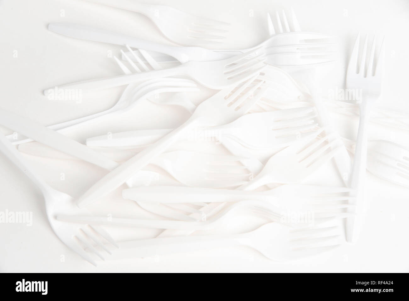 A bunch of white disposable single-use plastic forks commonly available all over the world. - Stock Image