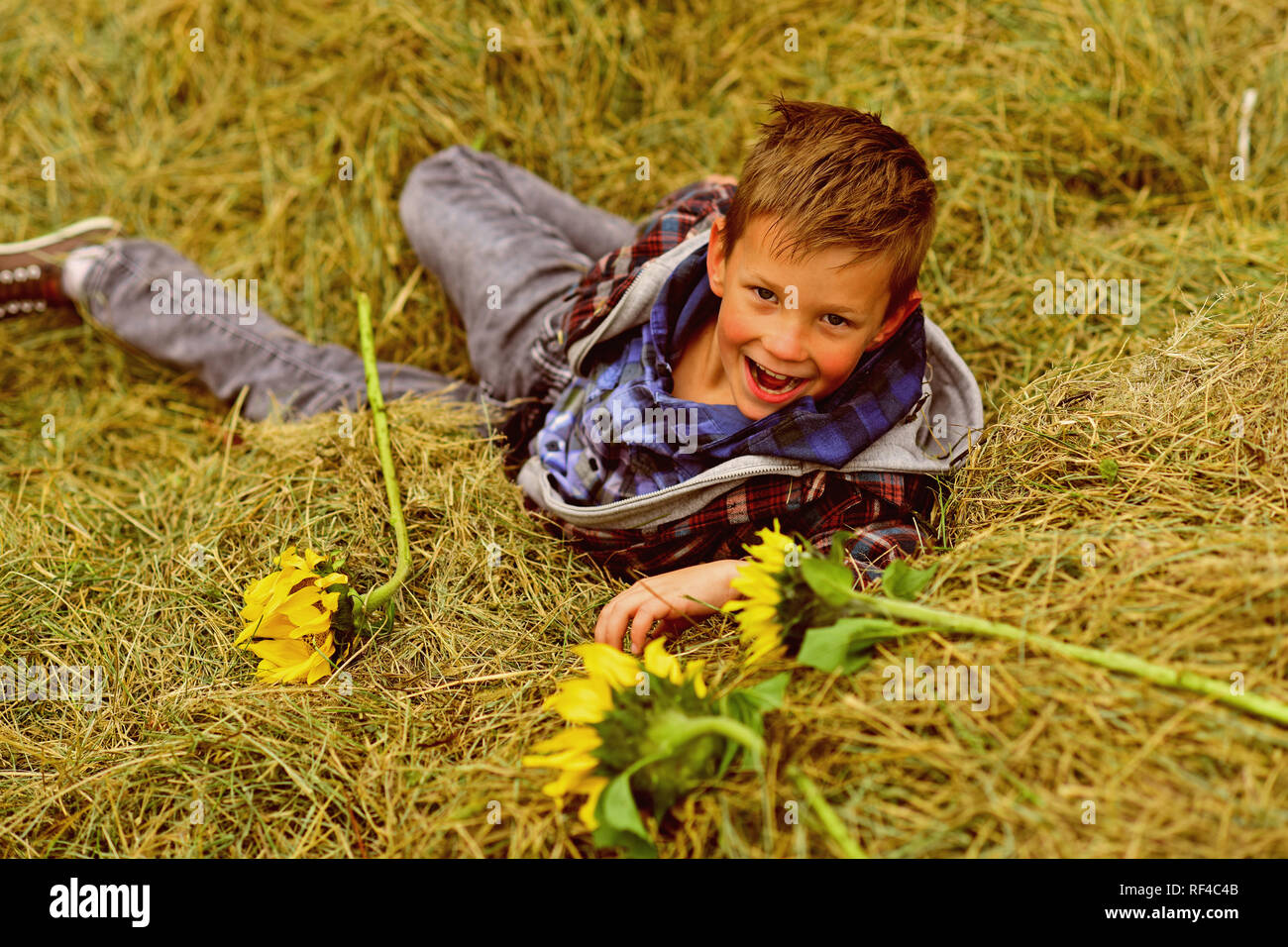 Happy childhood time. Happy boy. Little boy happy smiling in hay. Little child on farm. Play is the work of childhood - Stock Image