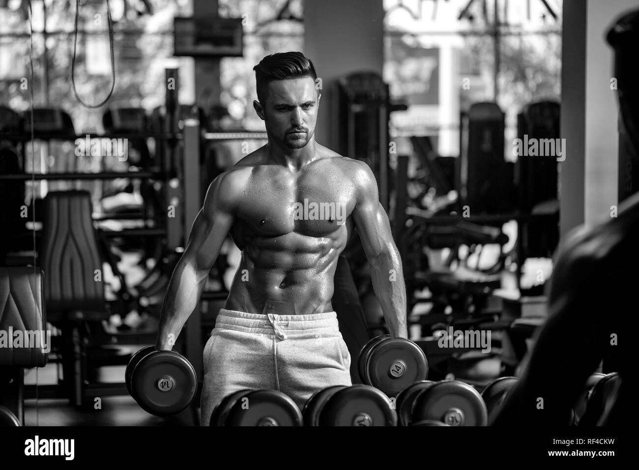 muscular man with dumbbell - Stock Image