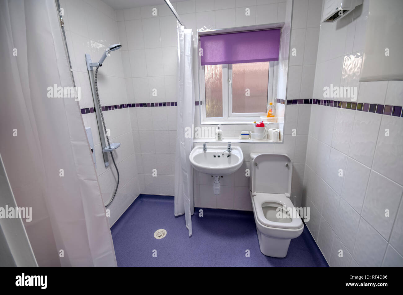 A wet shower room adaptation of a bathroom for use by a disabled or elderly person. - Stock Image