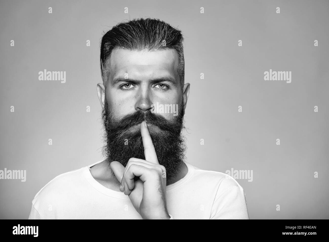 Bearded man with hush gesture - Stock Image