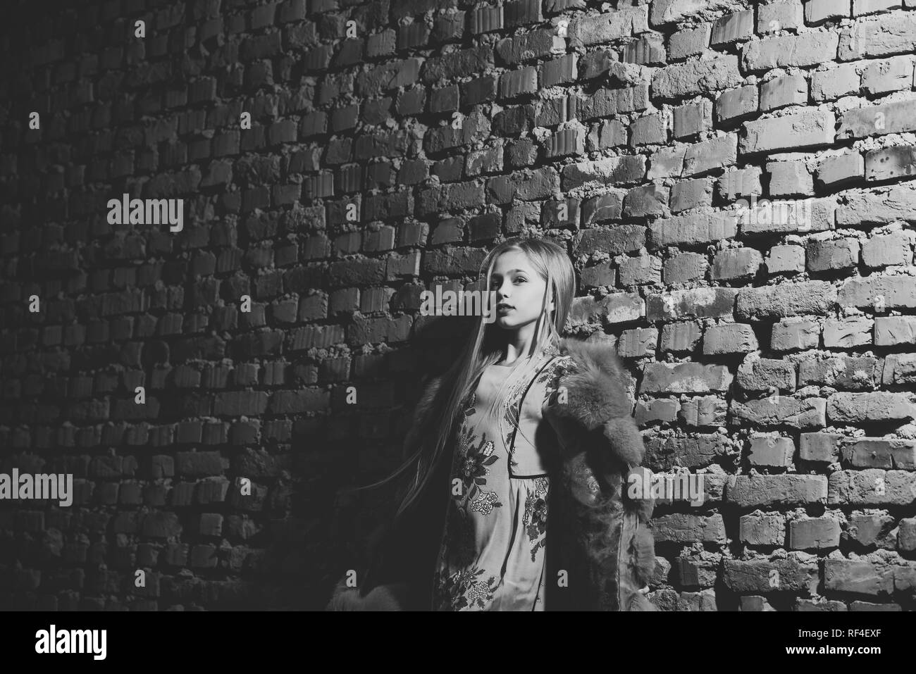 97d777361b Little girl pose in winter jacket on brick wall, fashion. Child model with  long