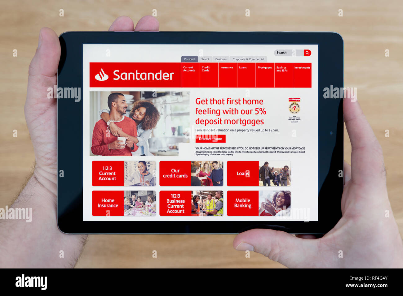 A man looks at the Santander Bank website on his iPad tablet device, shot against a wooden table top background (Editorial use only). - Stock Image