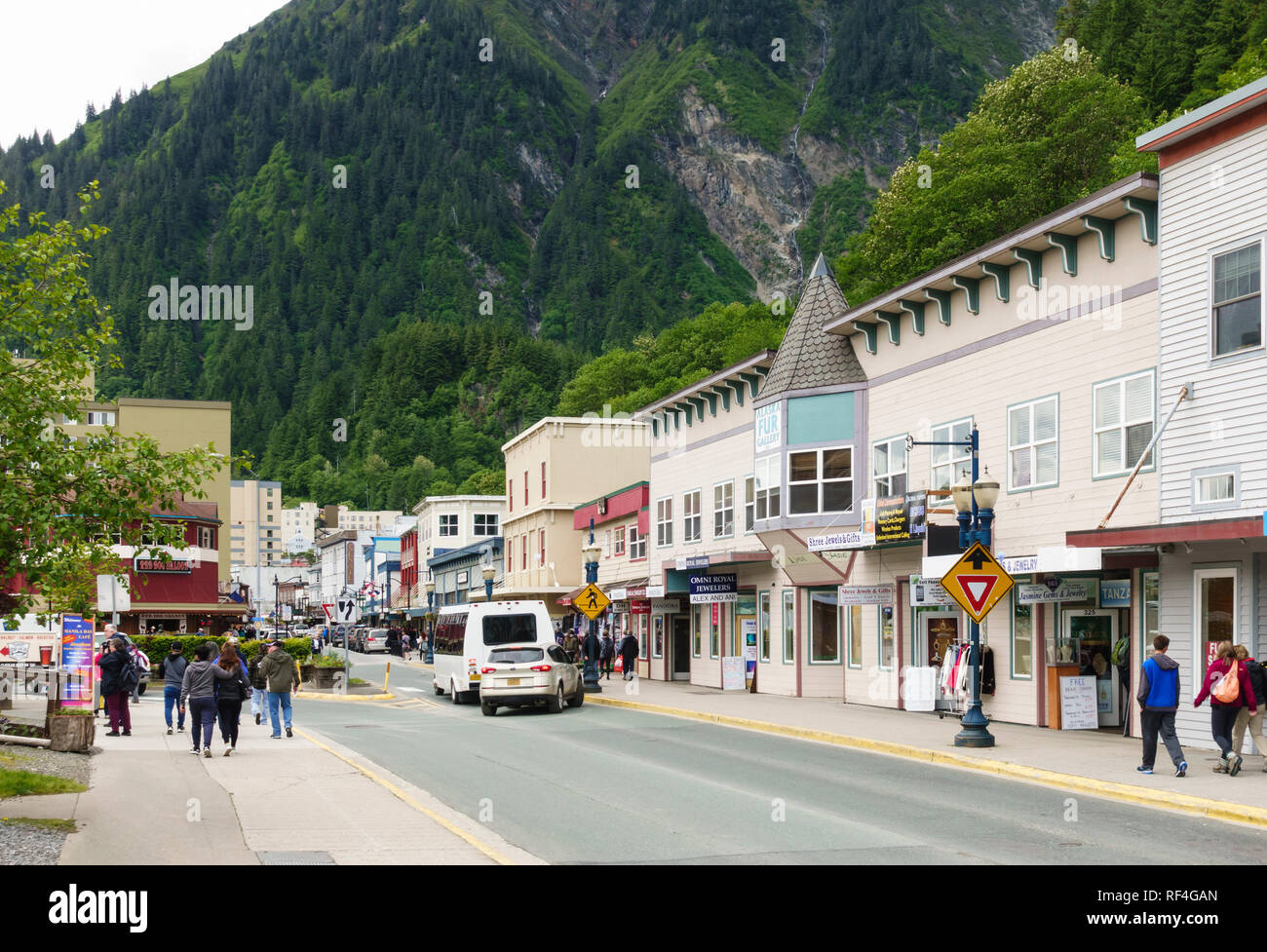 Tourists and sightseers visit shops and stores along S. Franklin Street in downtown Juneau, Alaska. Steep mountainsides provide a dramatic backdrop. - Stock Image