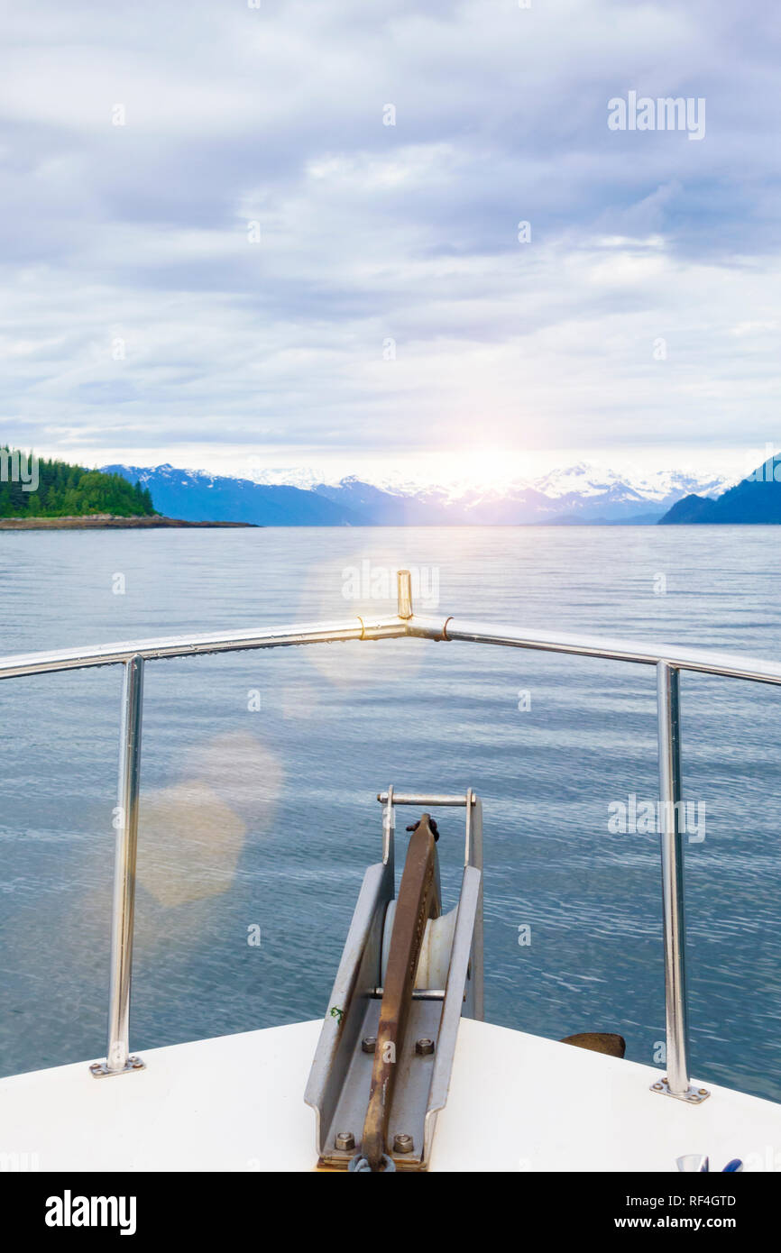 Motor crusing yacht in Glacier Bay National Park, Alaska. Sunset view of distant islands and snow-capped mountains over the bow of a motorboat. Stock Photo