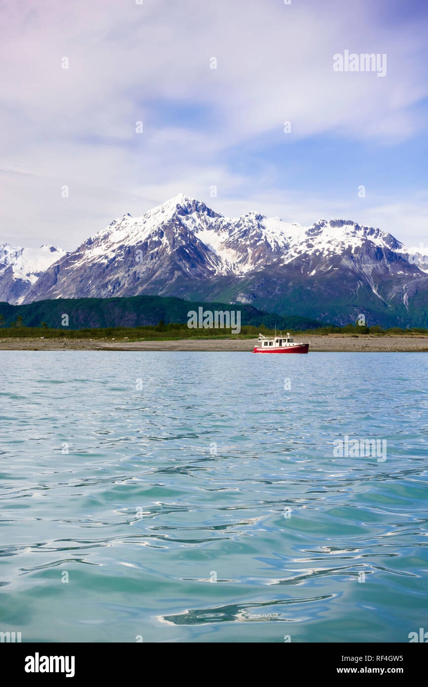 A motorboat motor cruising yacht anchored in a beautiful wilderness bay cove near snow-capped mountains, Glacier Bay National Park, Alaska, USA - Stock Image